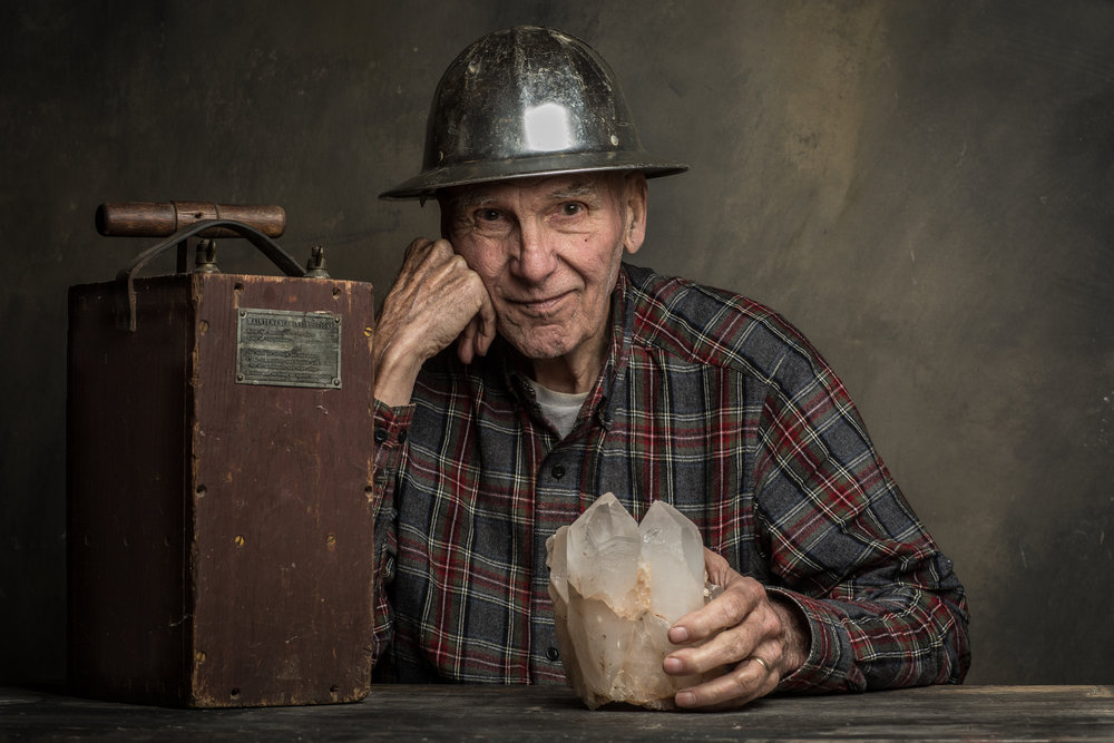 Third generation miner Frank C. Perham, 84, in West Paris, Maine. The family tradition all started when his grandfather's cows, moving from one area of a field to another, helped unearth a large feldspar deposit. From there, his grandfather helped get the feldspar mill going in 1926 and his father, Stanley, started a mineral store in 1919. Frank worked with his father when he was growing up and, like his father, earned a geology degree from Bates College. In the 1950s Frank also served a tour in Korea and became very skilled with explosives. Being good at placing explosives gave him work with the state of Maine for road construction projects, but also gave him the opportunity to mine on weekends. The pockets he's found over the years and discoveries he has made now sit on display at both The Smithsonian and as close as the Maine Mineral and Gem Museum in Bethel, Maine. Frank has given many lectures over the years and also has created a display of many of his finds in the basement of his home, where people stop in to hear his many stories and learn about Maine's minerals from someone with an unbridled passion for minerals and lifetime of experiences.