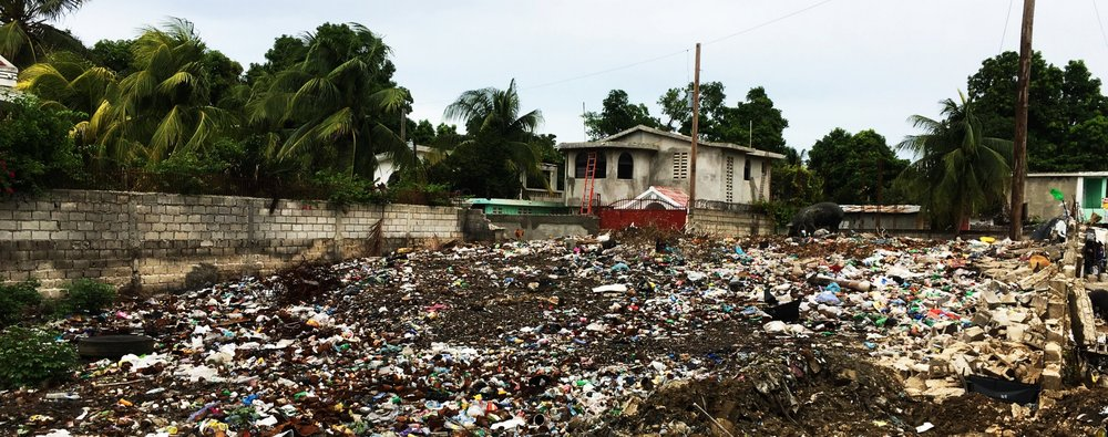 An empty lot in Tabarre, Port-au-Prince, overfilled with discarded local waste.