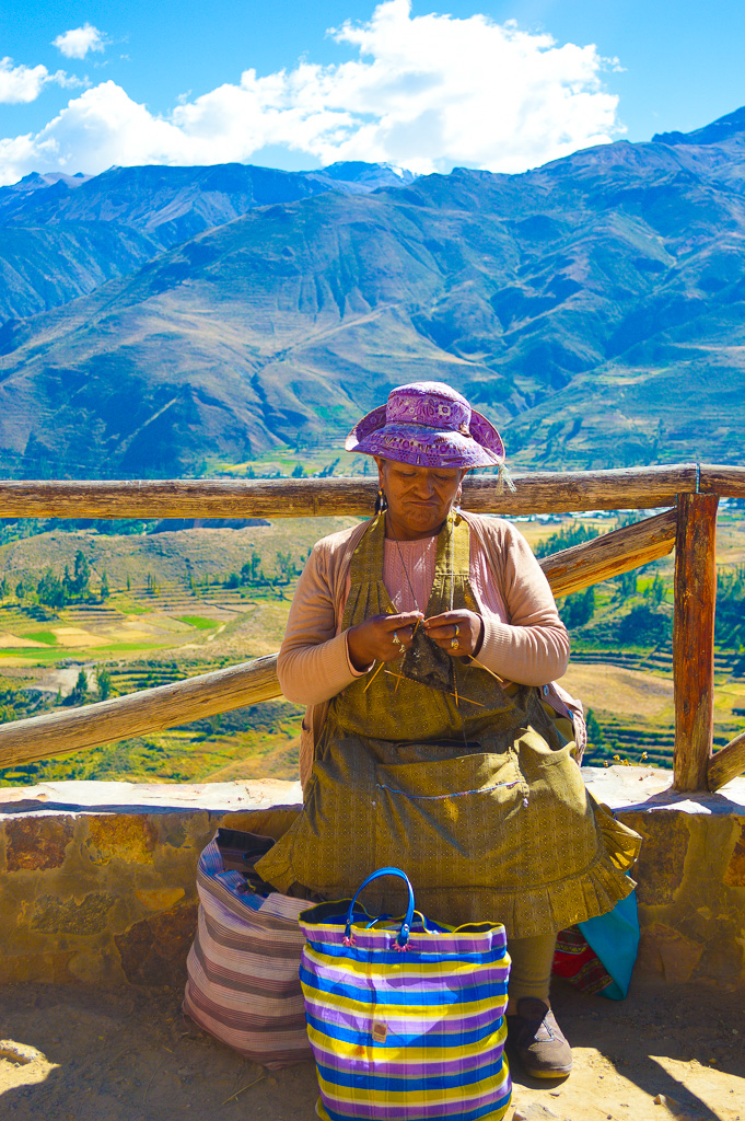 Peruvian woman knitting with rice field backdrop of colca canyon mountains
