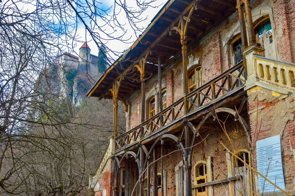 A derelict house with Bled castle looming above it