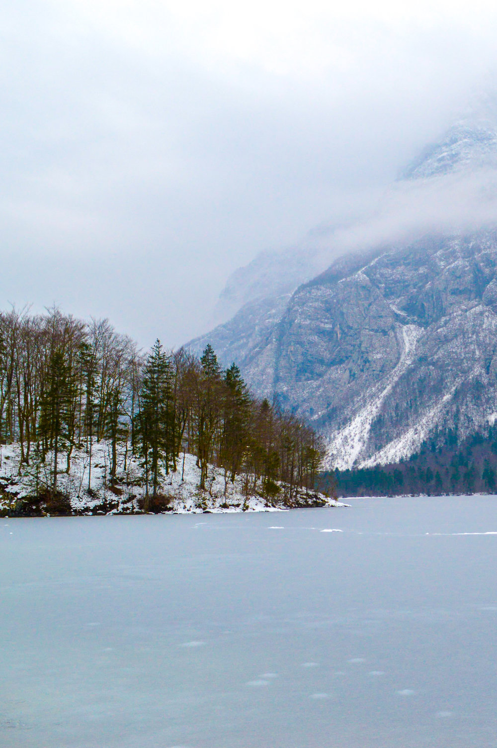 Completely frozen Lake Bohinj with a more dramatic mountainous backdrop