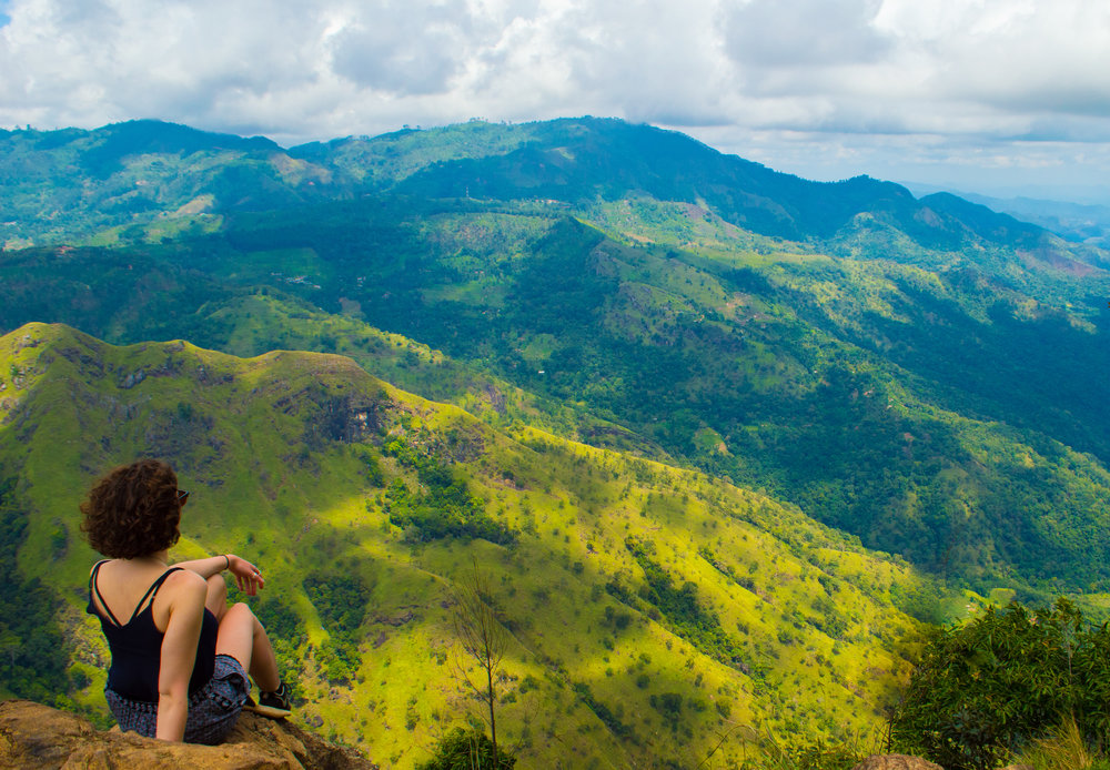 Sitting on a ledge at Ella Rock looking over towards Little Adam's Peak and the mountains beyond.