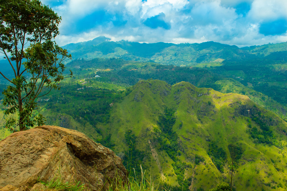 The protruding rock at the top of Ella Rock that you can sit on, with Little Adam's Peak and the mountains beyond.