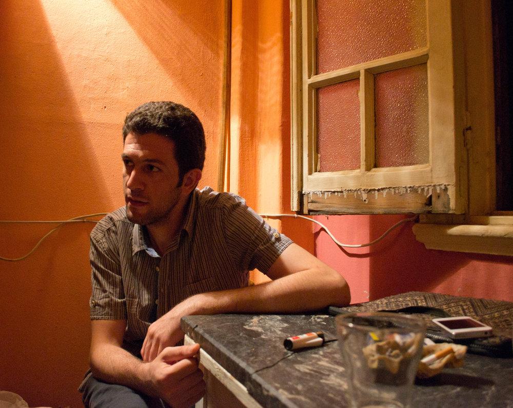 Nabil ryger smøger i det lille køkken i den lejlighed, han deler med to andre. Foto: Rasmus Bøgeskov Larsen