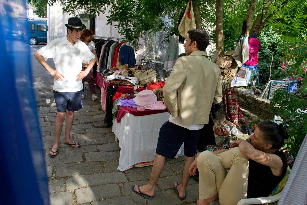 Nabil prøver tøj hos en brugthandler.Nabil handler brugt tøj på et søndagsmarked. Han er kommet i land i Italien uden andet tøj, end det han havde på da de sejlede ud fra Egypten samt en bluse han fik af en sømand på trawleren.