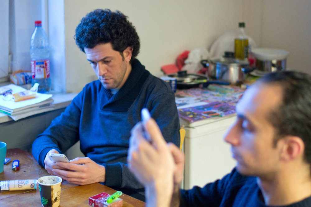 Nabil sidder på sit lille værelse på asylcentret (sammen med en syrisk ven). Hans iPhone er næstefter hans instrument hans vigtigste ejendel, for den holder ham i kontakt med venner og familie, som er spredt ud over tre kontinenter