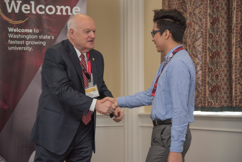 CWU President James Gaudino shakes hands with Fellow Carlos Barajas-Zamora.