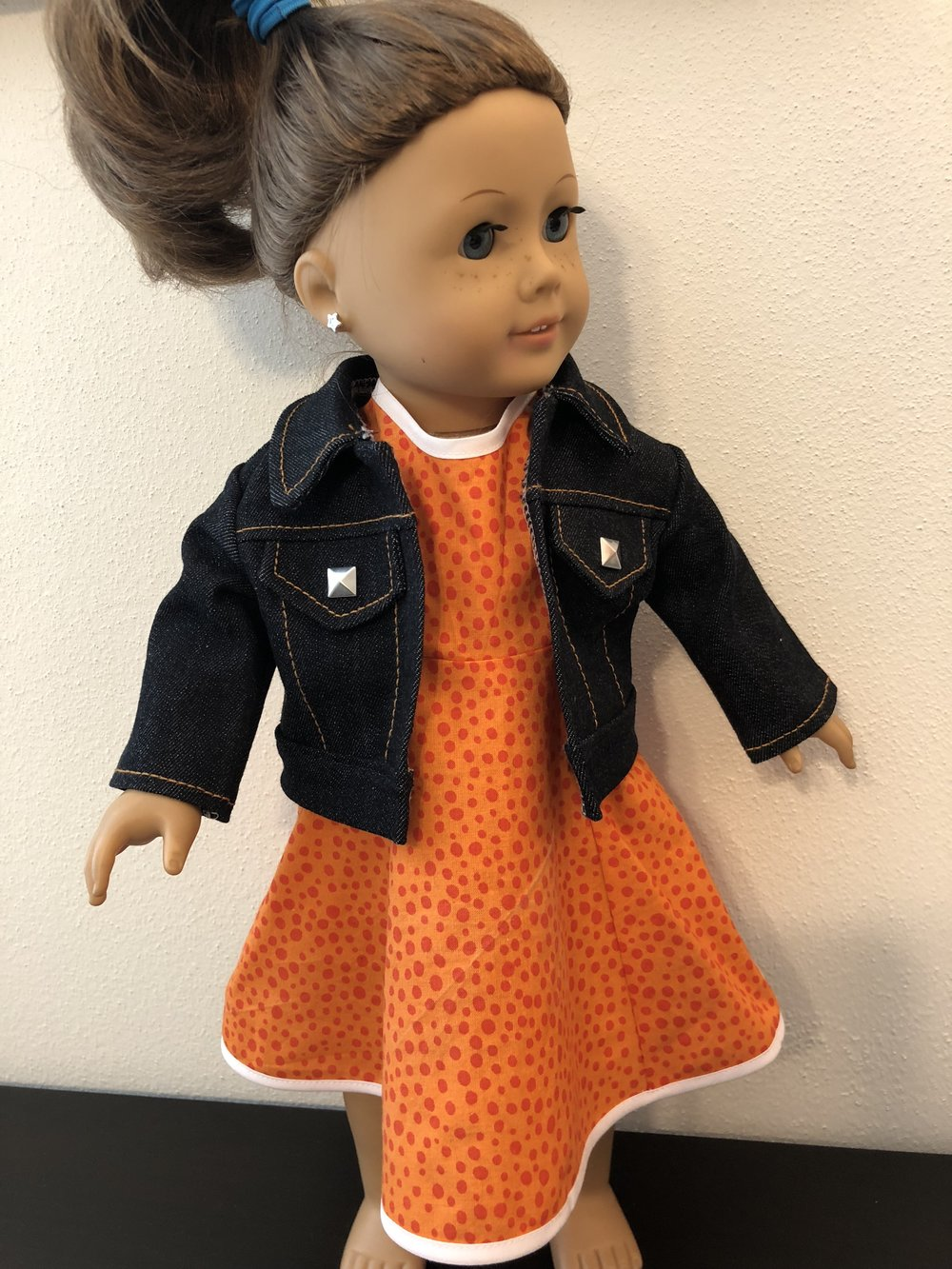 Dark wash denim jacket with studs and orange shift dress