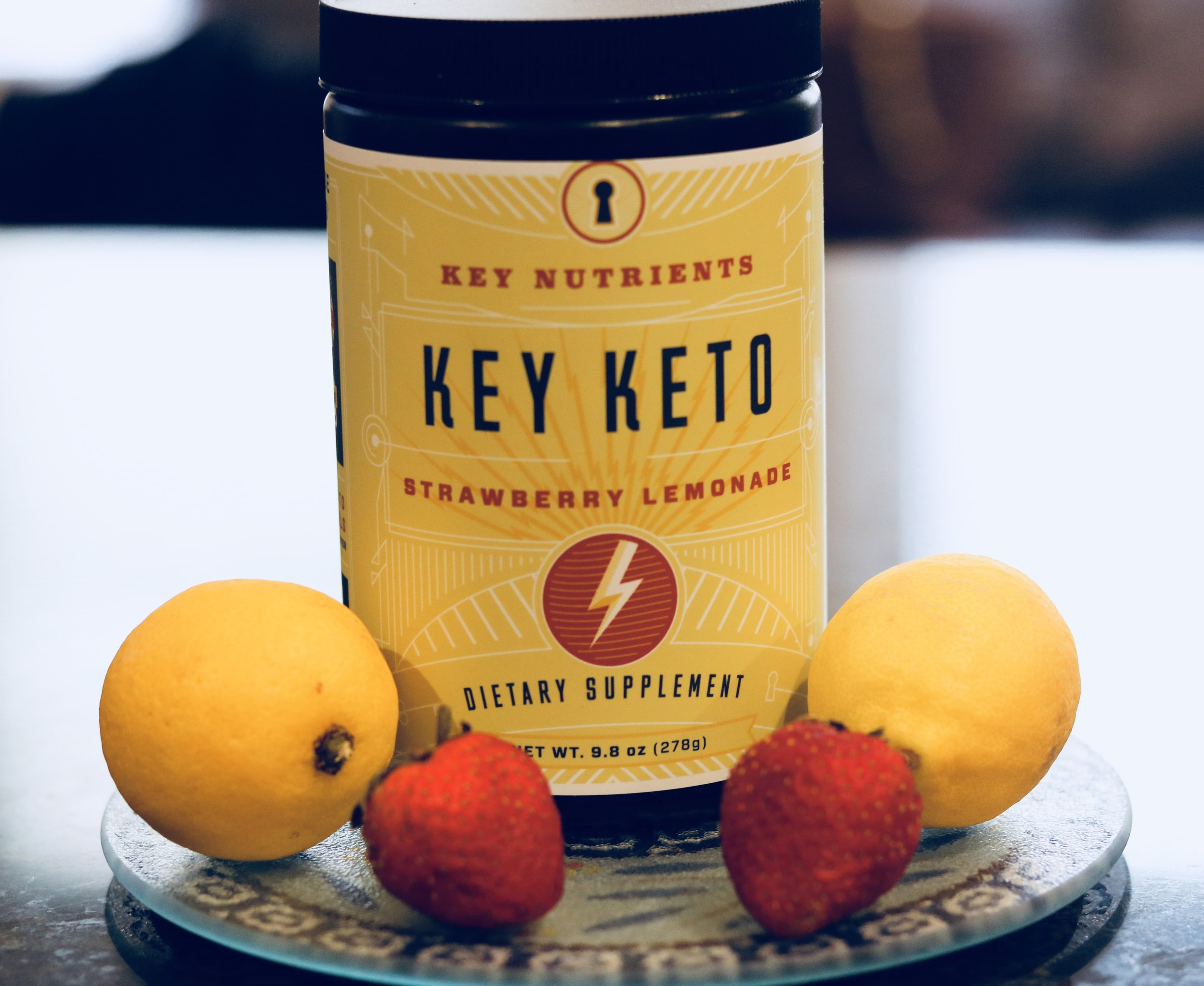 A container of Key Keto\'s Strawberry Lemonade power, along side two lemons and two strawberries