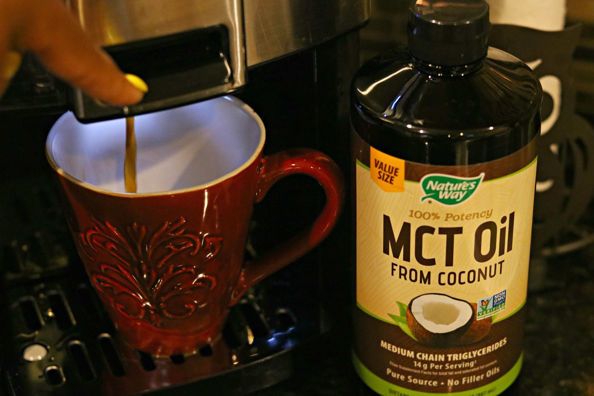 A bottle of Nature\'s Way MCT Oil next to a red mug of coffee