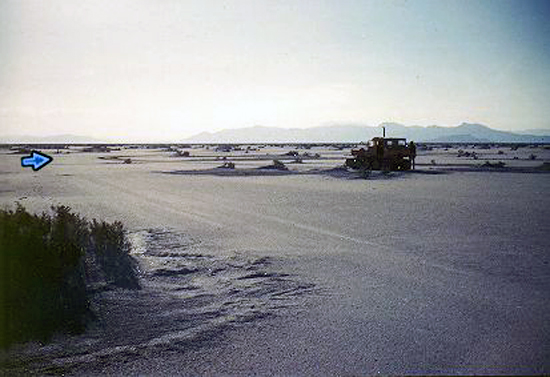 "13. Made 10/61, Great Salt Lake Desert, Utah. The Big Bend.   Photograph: Copyright © 1961 Roy D. Tea.   View looking west. Donner-Reed Trail at the ""Big Bend."" The trail runs from lower right to left center, then curves at the blue arrow to the right behind the trackmaster. The arrow points in the approximate direction the trail takes at this point which is northwest. Floating Island is the closer dark mountain just to the right of the Trackmaster. The mountain behind Floating Island and above the Trackmaster is Silver Island. Pilot Peak is the faint mountain on the distant skyline just left of the vehicle."