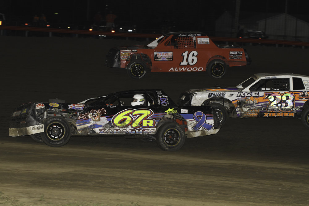 Jeremy Nichols (67R) navigates through lapped cars of Andrew Alwood (16) and Shawn Ziemer (23Z) on way to victory in the Fourth Annual What Up Dog Memorial Race.  A.E. Blair Photography Photo