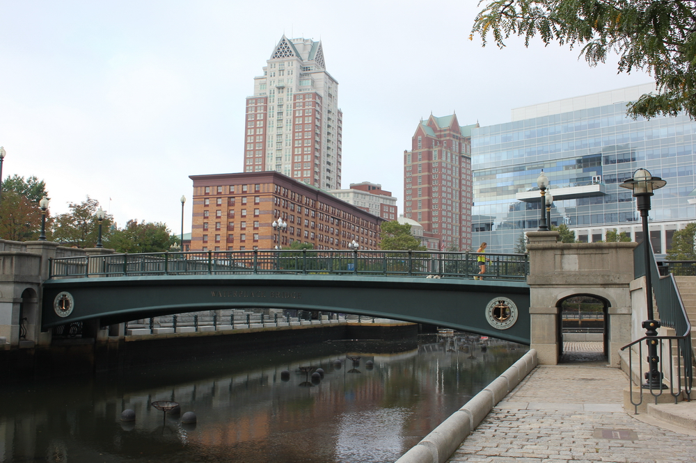 """... enjoy a lovely stroll by the river past Venice inspired bridges or see some wonderful public art, all at this well-designed four-acre park and scenic riverwalk ..."" (from Trip Advisor).  Waterplace bridge over the Woonasquatucket River in downtown Providence, Rhode Island, USA (September 2017) (the braziers seen in the stream are lit for the  WaterFire Providence  Arts Festival)."