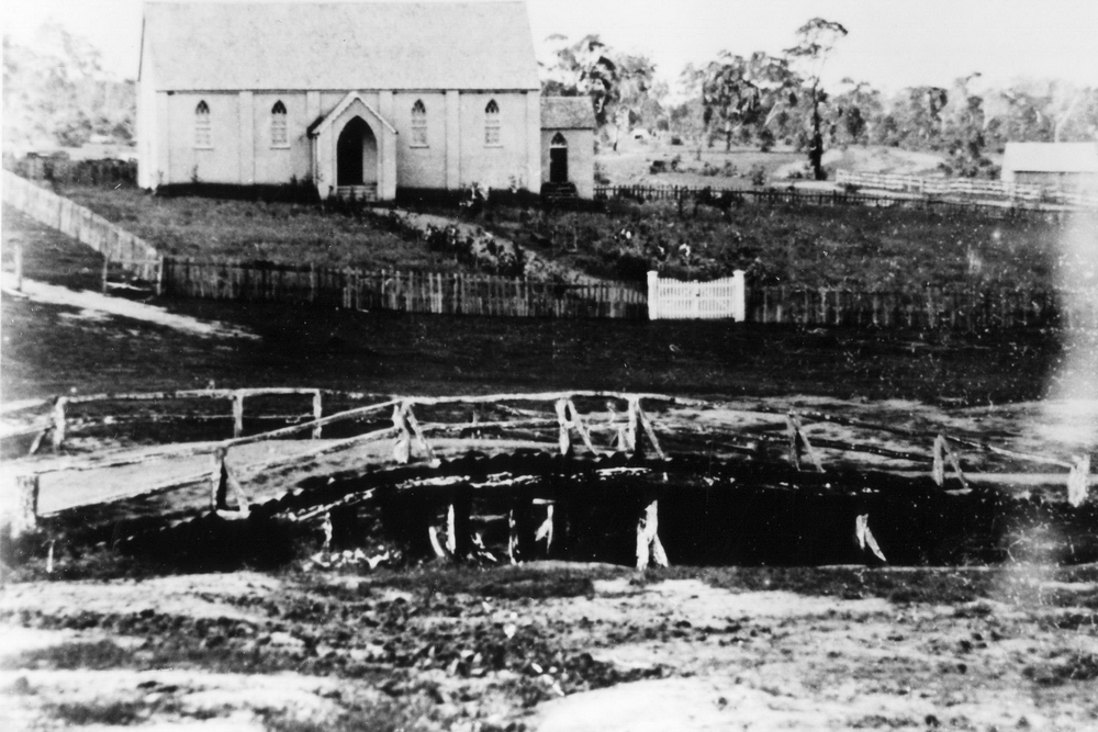 The first bridge across Dumaresq Creek, Trim bridge, with the Presbyterian Church in the background - early 1900s