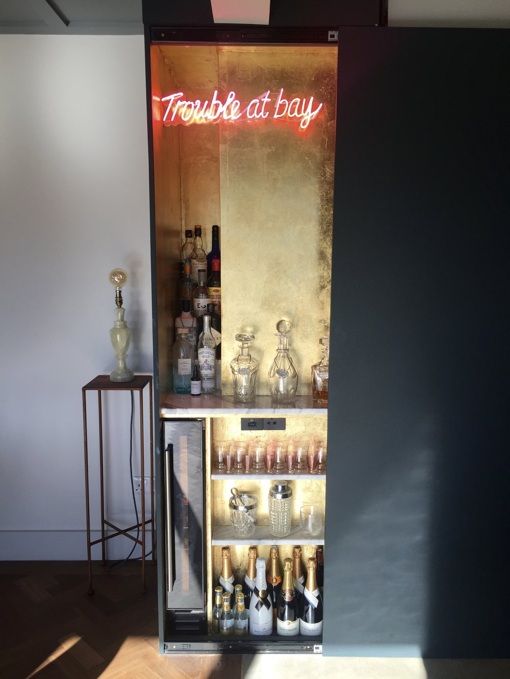Behind the Black Blue sliding wall Michaela has added gold leaf, neon and carrera marble shelves to make this fabulously stylish hidden bar area    @theoldpiggery