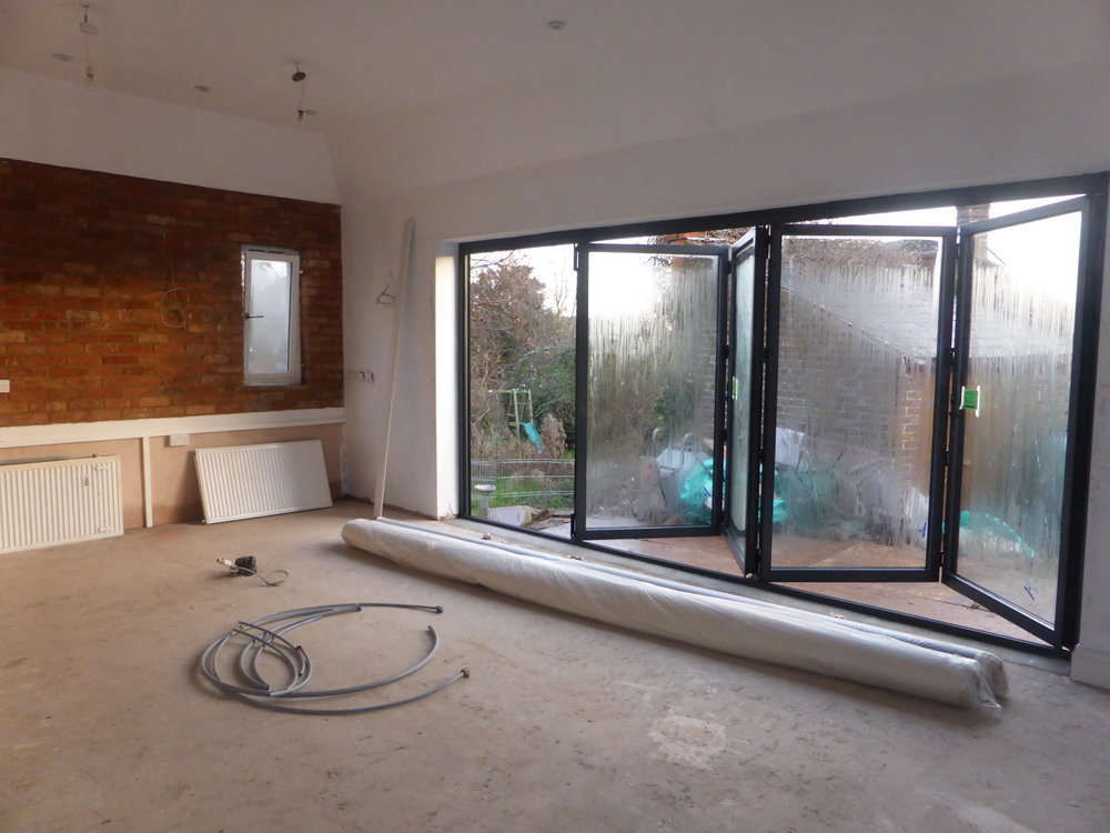 Bifolds in and first mist coat of paint on the walls....... No idea why those radiators are there?
