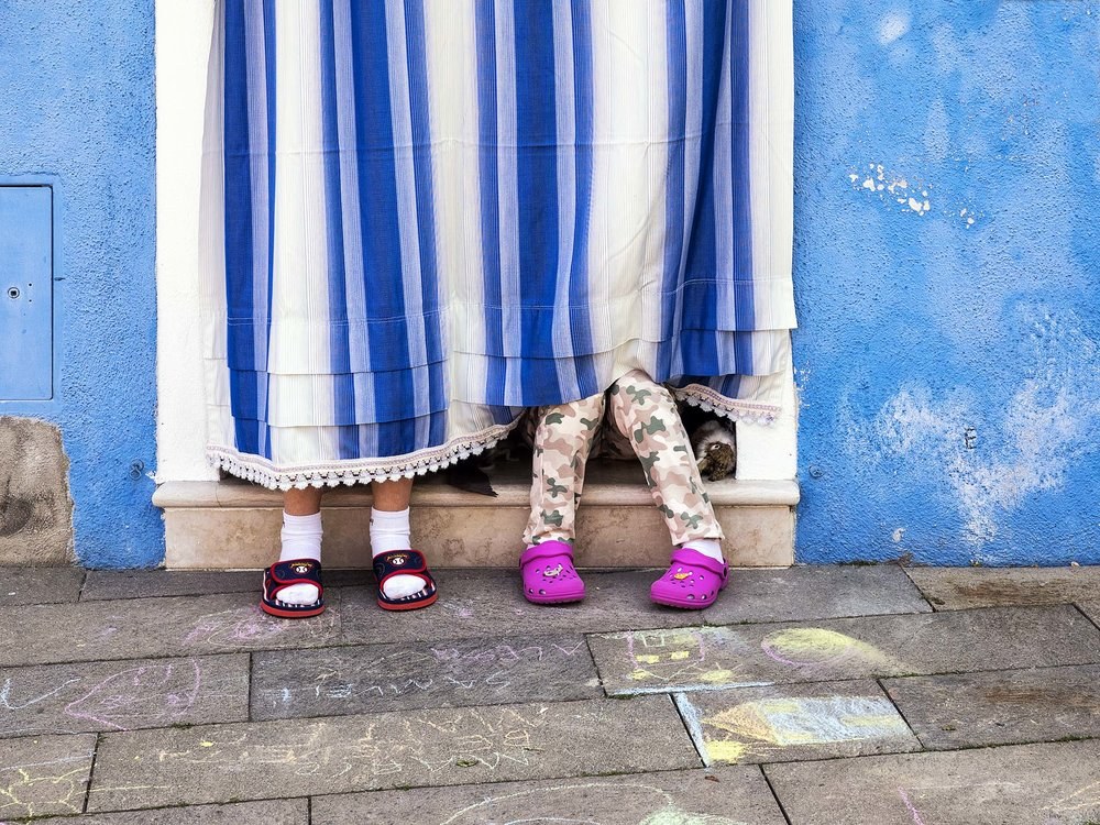 Children behind the doorway curtain - Burano (Venice), Italy