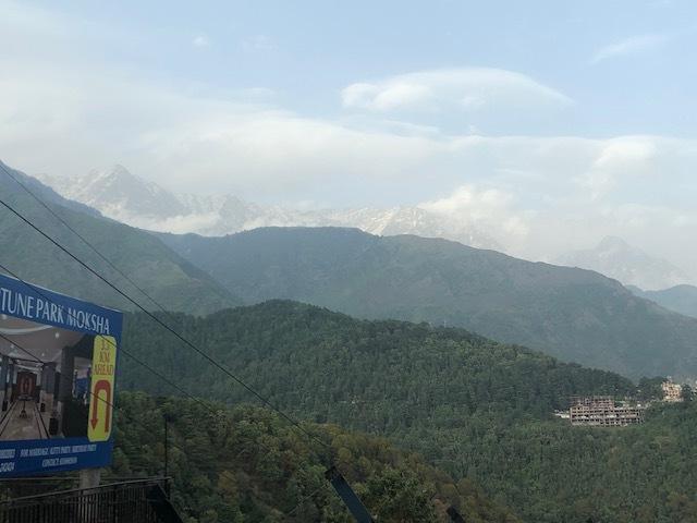 Vy på väg upp mot Dharamshala med de snötäckta alptopparna i bakgrunden