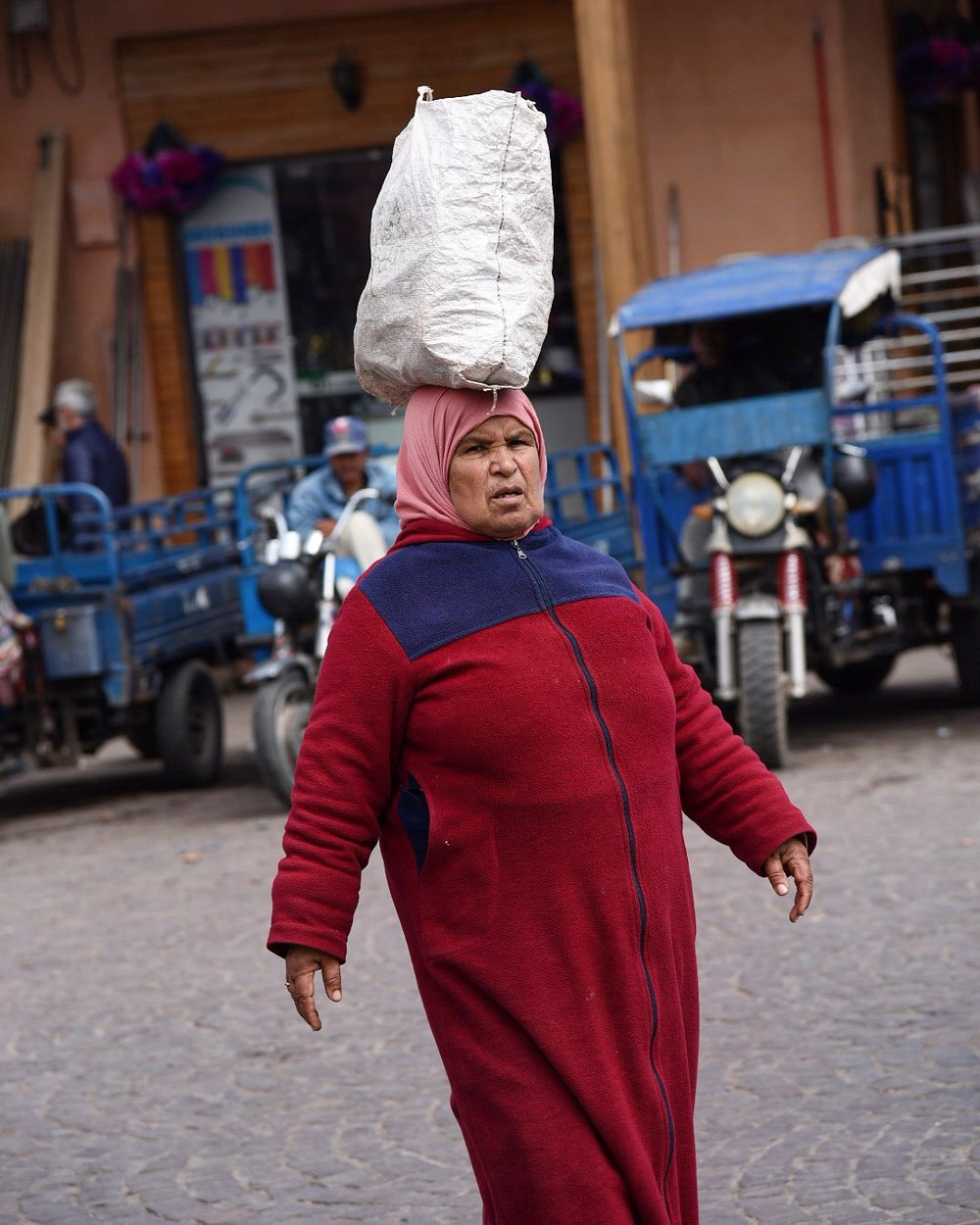 A woman carries a bundle on her head while walking in Marrakesh