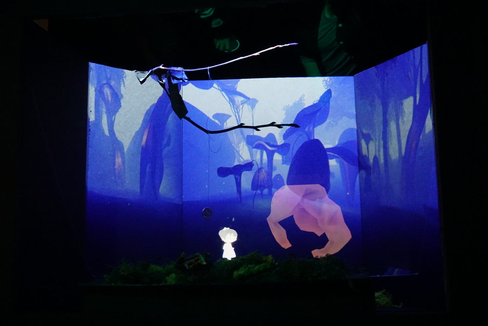 Scene 1 - The Gatekeeper - The Unreal Engine world is projected in the back of the box and the characters are projected into what appears to be 3D space in the mid-ground by the technique of Pepper's Ghost.  In the foreground there are physical forrest features that the audience can interact with.