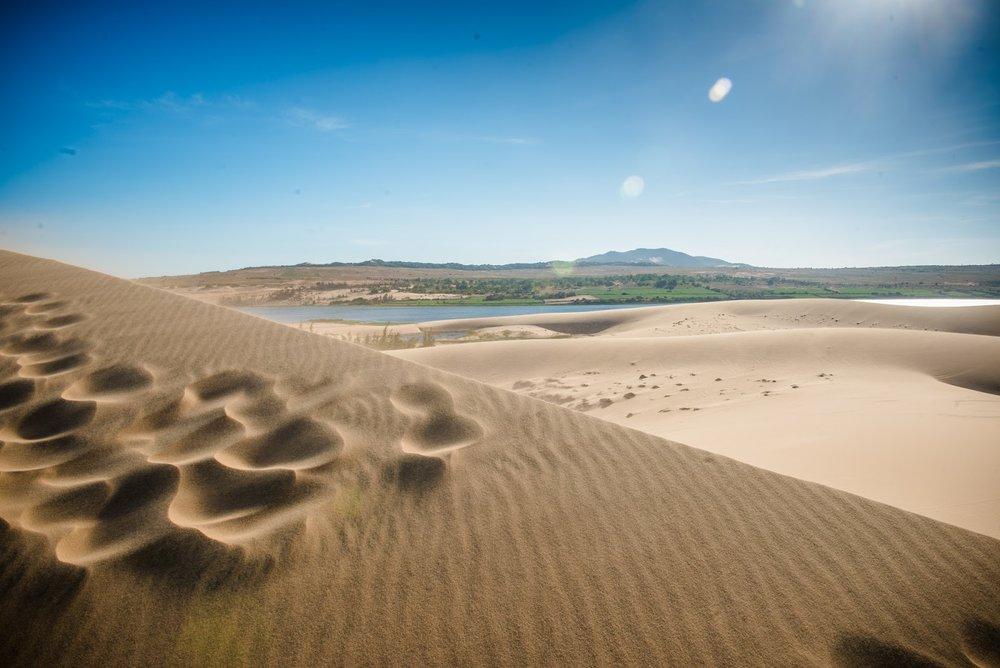 ….White Sand Dunes..Đồi cát trắng…. - ….45 minutes up the coast, Mui Ne's famous white sand dunes sit nestled against the edges of Bau Trang Lake. A favourite for many, tours to the white sand dunes take visitors wandering through the vast, wind-sculpted landscape- a common scene in Saharan Africa, but here in Vietnam it is quite unique.Visit at sunrise or sunset for maximum visual impact..45 phút lái xe dọc theo bờ biển, đồi cát trắng nổi tiếng Mũi Né nép mình bên hồ Bàu Trắng. Đây là sở thích đối với nhiều du khách, chuyến tham quan đồi cát mang đến cho quý khách trải nghiệm được lang thang giữa một nơi rộng lớn, phong cảnh hữu tình – một hình ảnh quen thuộc ở sa mạc Sahara Châu Phi, nhưng khá độc đáo chỉ có ở Việt Nam.Hãy ghé đến nơi này để chiêm ngưỡng tận mắt quang cảnh lúc bình mình hoặc hoàng hôn tuyệt đẹp….