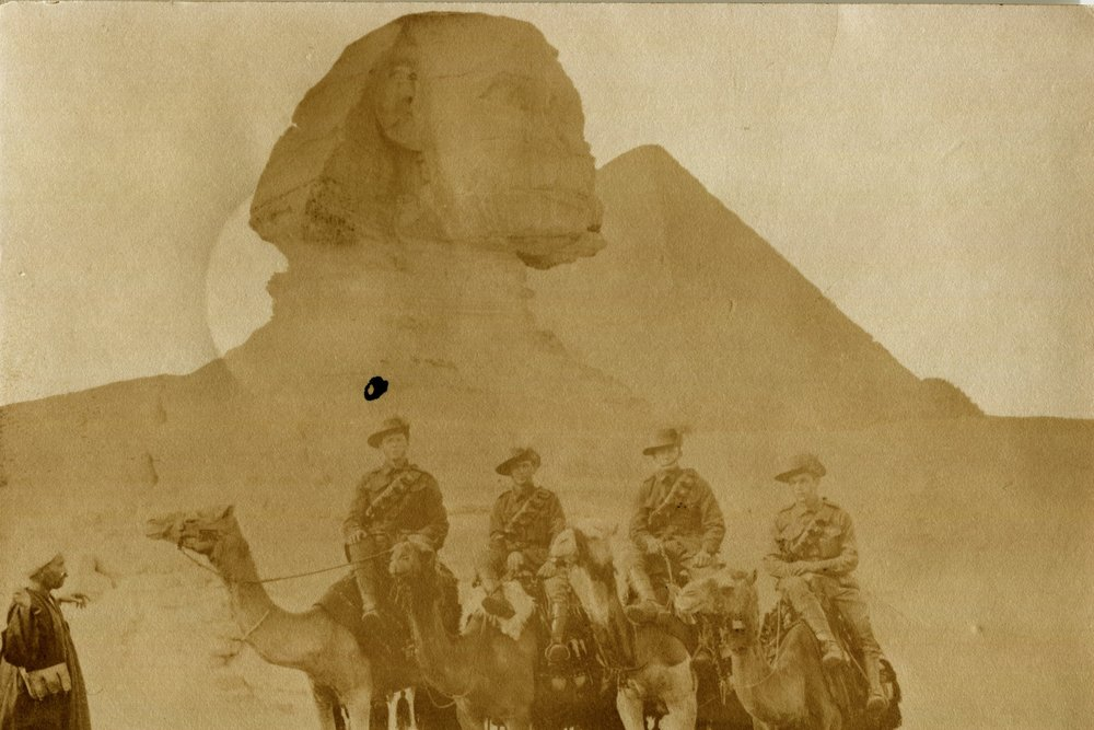 "L-R: Reg, Moreland 'Morey' Jones, Cliff McWhirter, and Will Gillespie visiting the Pyramid of Cheops on 19 December 1915. ""This is a bad photo but as we paid in advance for them, it's just a matter of looking pleasant. It's good sport, riding round the Pyramids on donkeys. There are excavations in all directions showing up ancient ruins."""