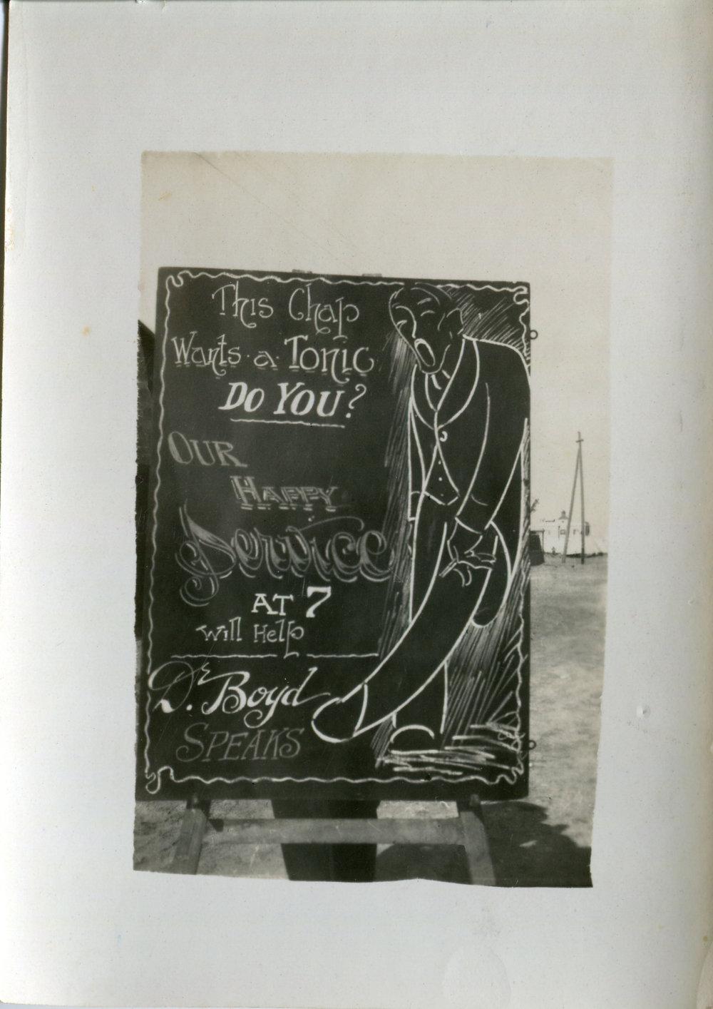 Reg's chalkboard advertising Dr Boyd's service. Reg's drawing implies the 'tonic' this chap needs is one to treat the syphilis affecting his left knee...