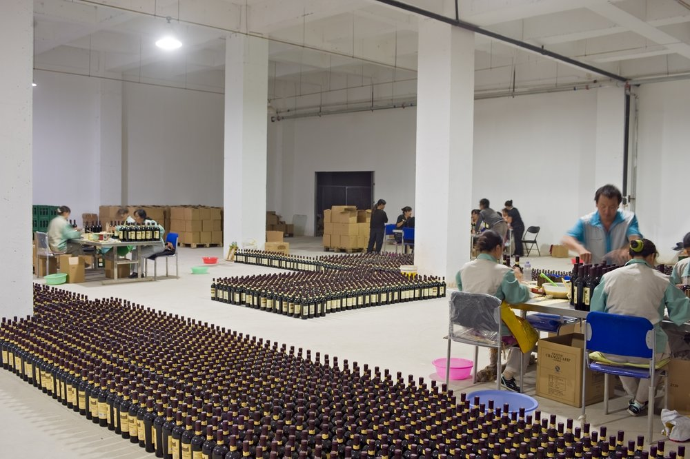 Only in China would you see the staff hand gluing labels on one million bottles of wine.