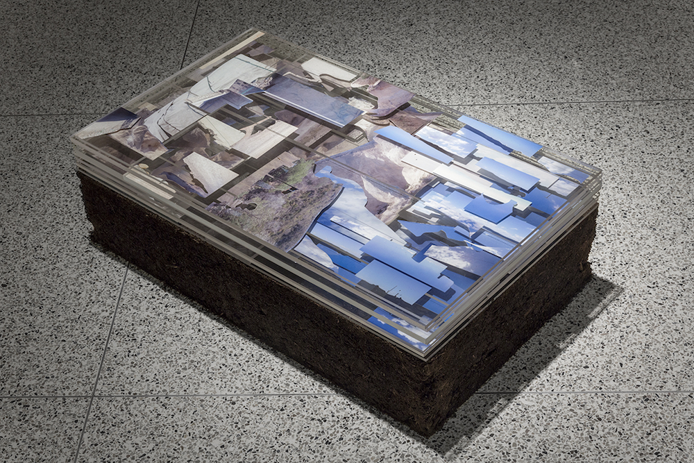 Cut digital photographs from Haitian-Dominican borderlands layered in plexiglass on pedestal of rammed earth.