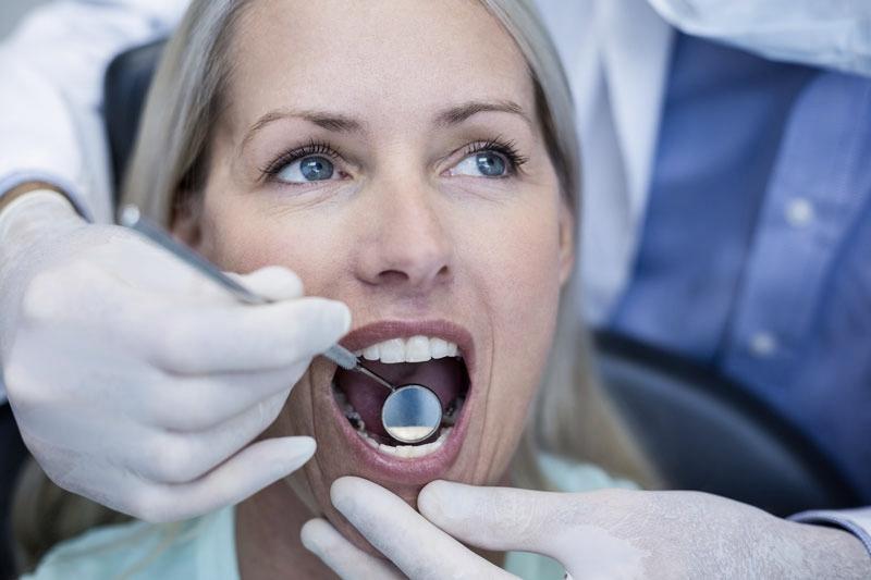 Blonde lady having dental exam following dental pain