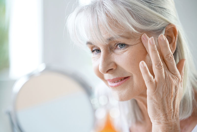Older lady looking in the mirror and considering facial aesthetics