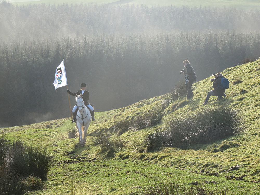 Krystal carrying the Lockerbie banner, on her horse Rebel, up Burnswark (Photo: Jessica Wheeler)