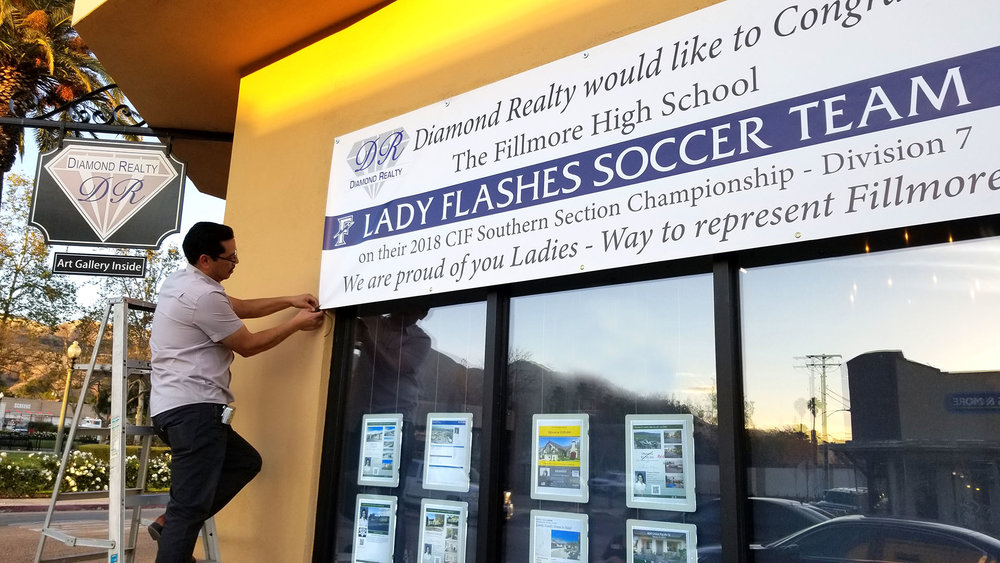 Diamond Realty Co-Owner Henry Robledo hanging a banner to congratulate the Fillmore High School Girls Soccer Team's CIF Championship win.