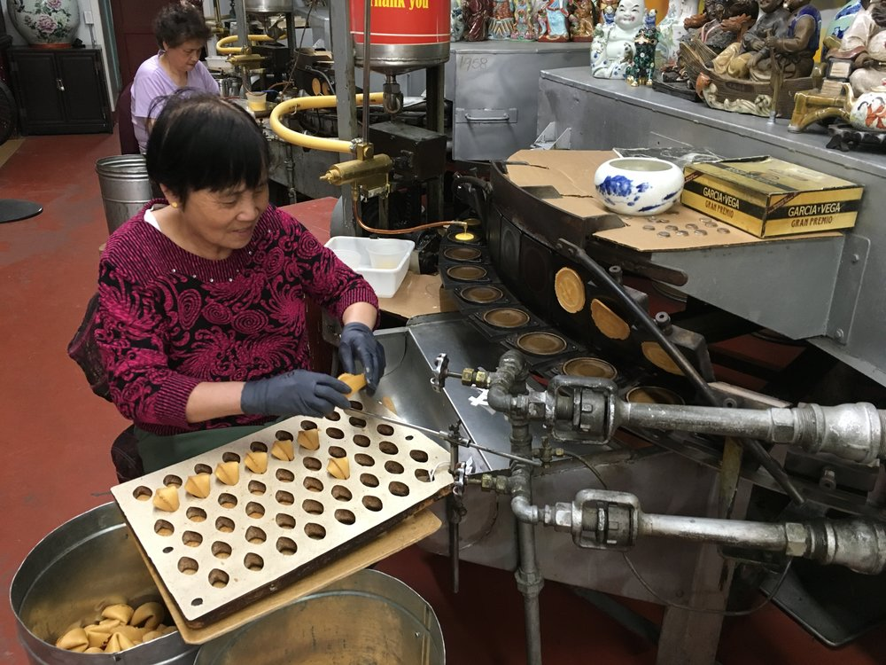 A worker making fortune cookies at the Golden Gate Fortune Cookie Factory