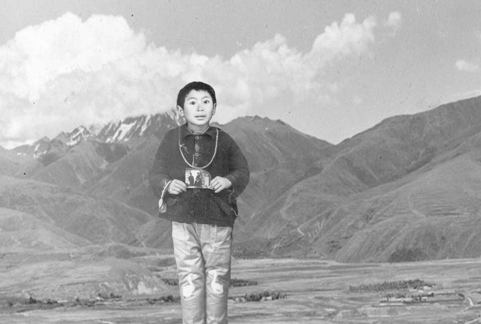 Eight-year-old Lelung Rinpoche, holding a photograph of his uncle. At age 12, Rinpoche began studying at Drepung Monastery in India on the advice of Ling Rinpoche