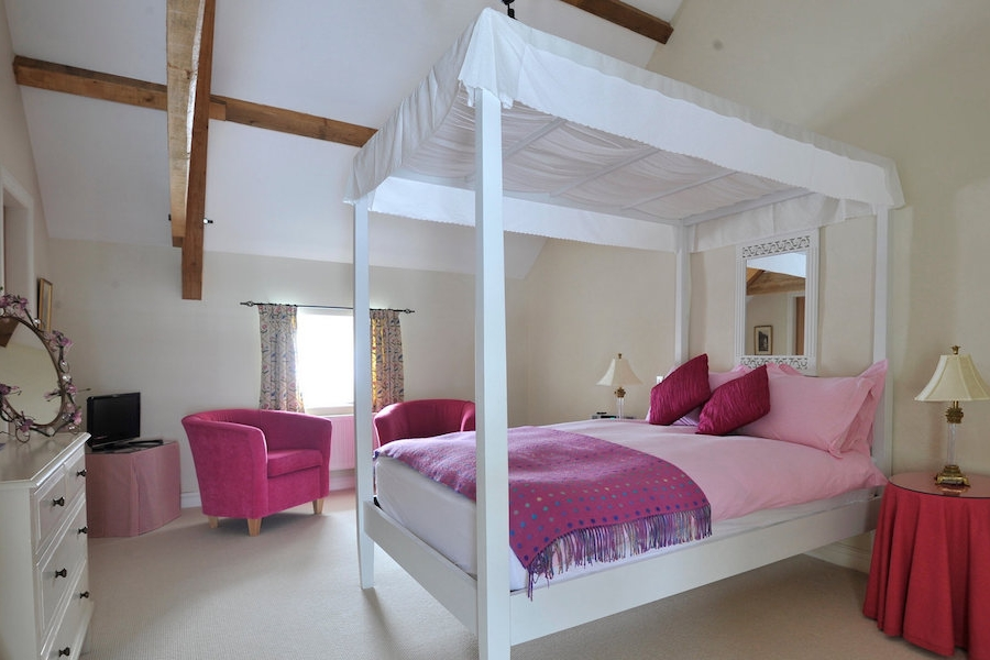 The Button's Room - One of two first-floor bedrooms – this one is named after Anna Wild Wales founder and daughter of The Outbuildings owner, Bun. The four poster is the focal point set under wooden beams and high ceilings. Views across to the tennis court and open farmland beyond – a blissful retreat.En-suite bathroom.