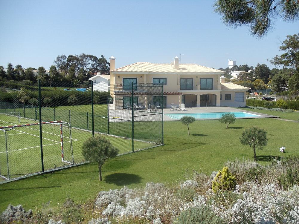 Cette maison dispose d'une piscine et d'un cours de tennis ou football privés
