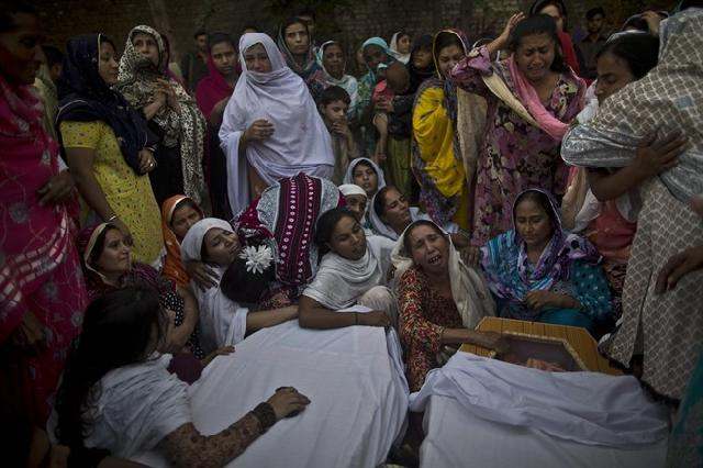 Pakistani women grieve over coffins of their relatives who were killed in the suicide attack on a church. (AP photo)