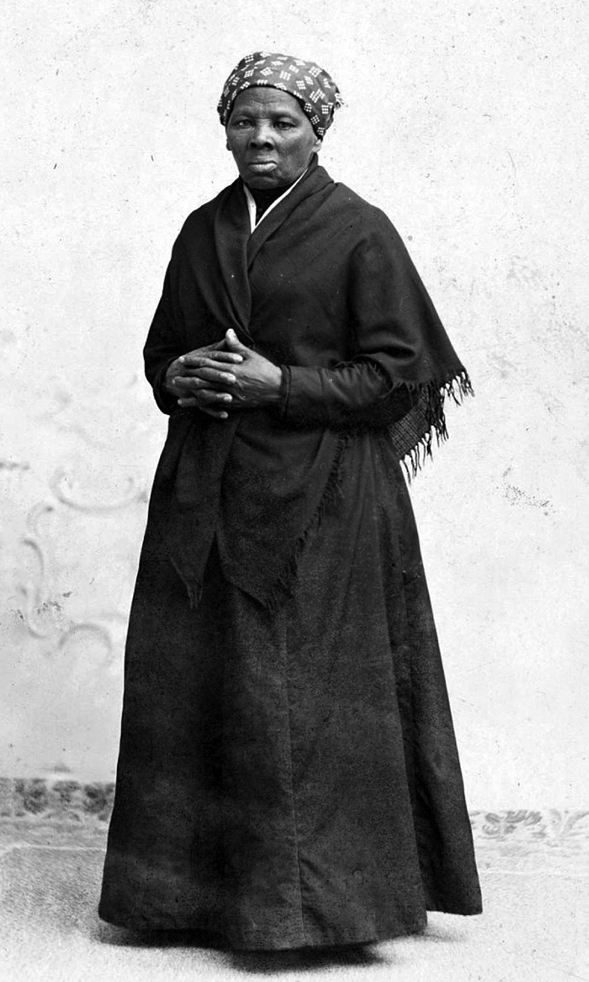 Black and white picture of Harriet Tubman standing, with hands folded
