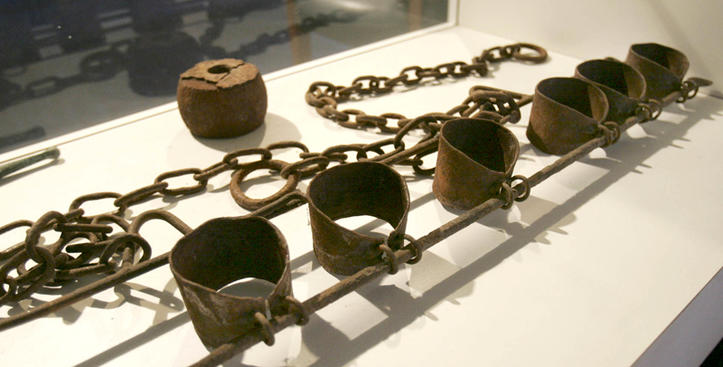 Picture of historical shackles and chains on display in a museum.