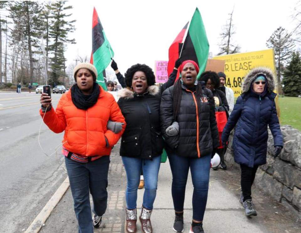 Photo of three black women marching arm in arm towards the camera, with black power flags behind them.