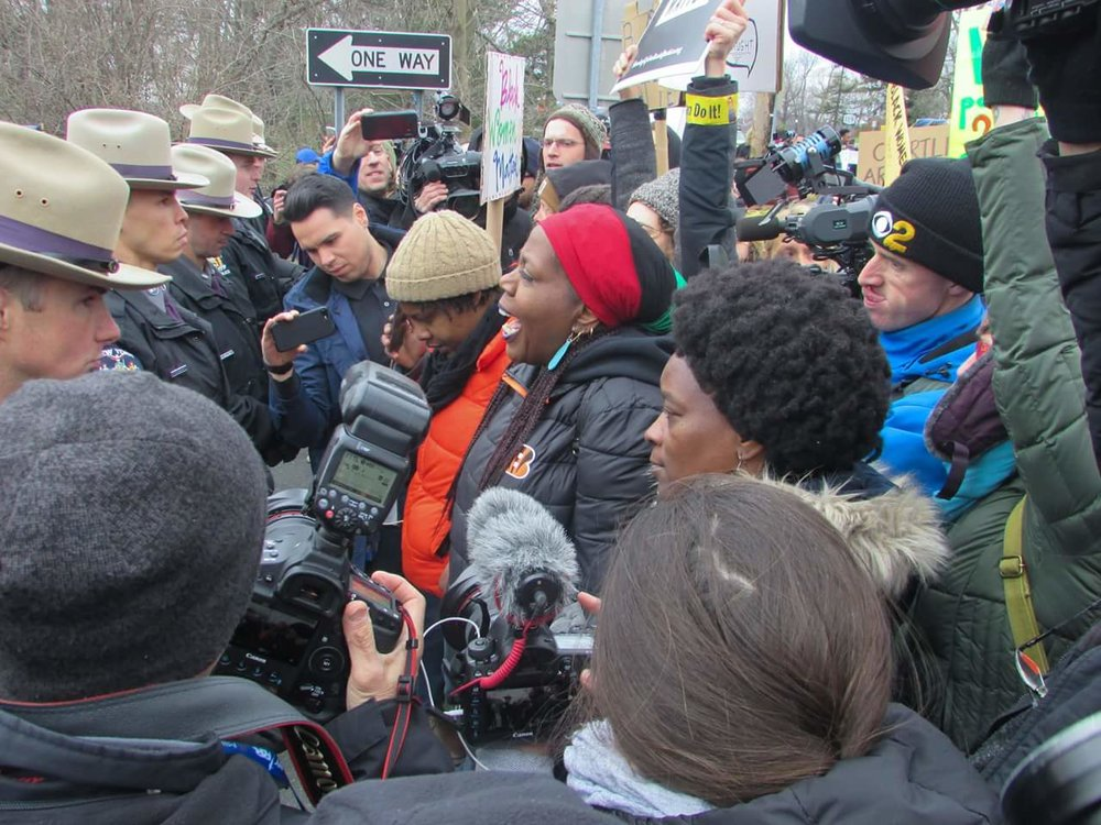 Photo of Vanessa Green chanting, standing in front of a line of state troopers. Other marchers and news media stand behind Vanessa.