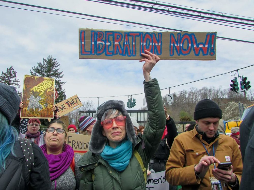 "Photo of white marchers marching towards the camera holding signs that say ""Liberation Now!"", ""Believe Them"", ""Eradicate Poverty"" and ""Black Lives Matter""."