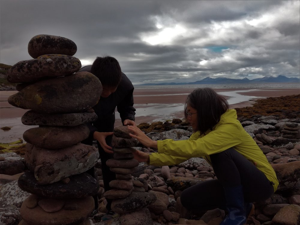 Balancing stones on a beach near Applecross with Skye in the background