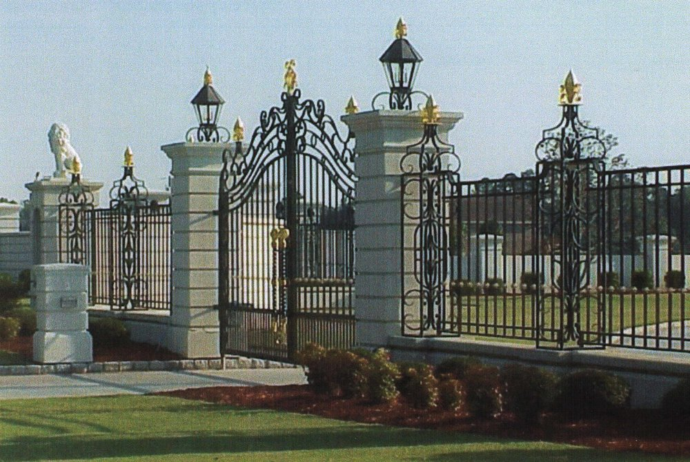 ornate driveway fencing and gate with gold leaf