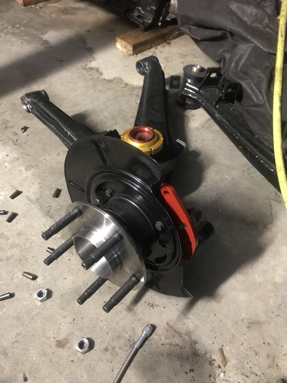 Rear trailing arm with Z4 hub installed and custom made brake caliper adapter.