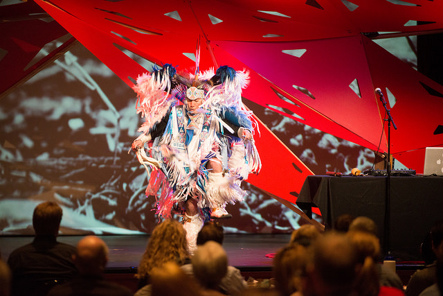 Native American dancer, hip hop artist, flutist, and comedian, Supaman, on stage.