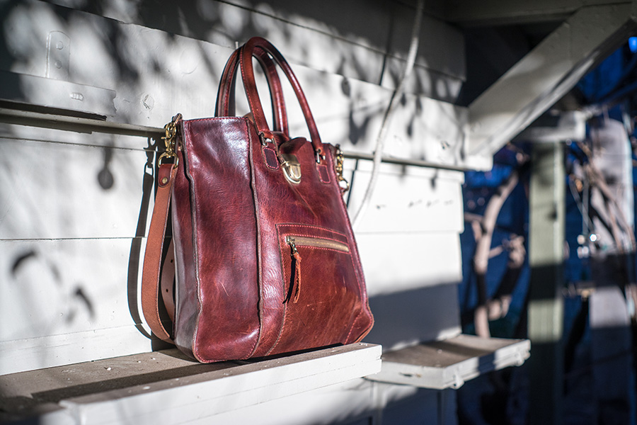 """I needed a ""daily driver"" something versatile that I could take with me every day; more than a briefcase, but less than a backpack. I wanted something that I could stuff my laptop into or my running shoes. I saw the Karl and thought it would be perfect. The form and design are rugged; but the color (cognac) and the hardware make it look elegant, I think the Karl is right on the crux of beauty and brawn -- just what I wanted! As a bike commuter, I wanted to make sure the bag fit snug against my body so I could throw it across my back when I was riding. I had Chris punch a few extra holes in the strap so that I could tighten the bag against my body. That might seem ""simple enough"" but I can't imagine walking into Bottega Veneta, Gucci or Prada saying ""I need your bag to be modified, can you punch a few holes here"" I would be laughed at. Chris on the other hand, welcomed the personalization. I have this bag with me almost 7 days a week, it goes to the gym, it goes to work with a roll of architecture plans between the handles, I take it grocery shopping, or sometimes if I'm just out for a walk and need a place for my water bottle and camera. The side that rubs against my body is developing a deep and dark patina, it has become as smooth as marble with rich but subtle changes in color. I like how it's aging so much that I occasionally flip the bag around so that my body starts rubbing on the front, hoping that I can achieve similar aging characteristic on the outward facing side. One tiny downside is that I cannot use the cellphone pocket inside, that is because it's stuffed with Chris' business cards for when I get stopped by strangers and questioned about my Karl. After the strangers inevitably praise the bag, there's something very satisfying about telling them ""thanks, my friend made it for me in Downtown LA""  Our Ambassador, Michael. Los Angeles, CA"