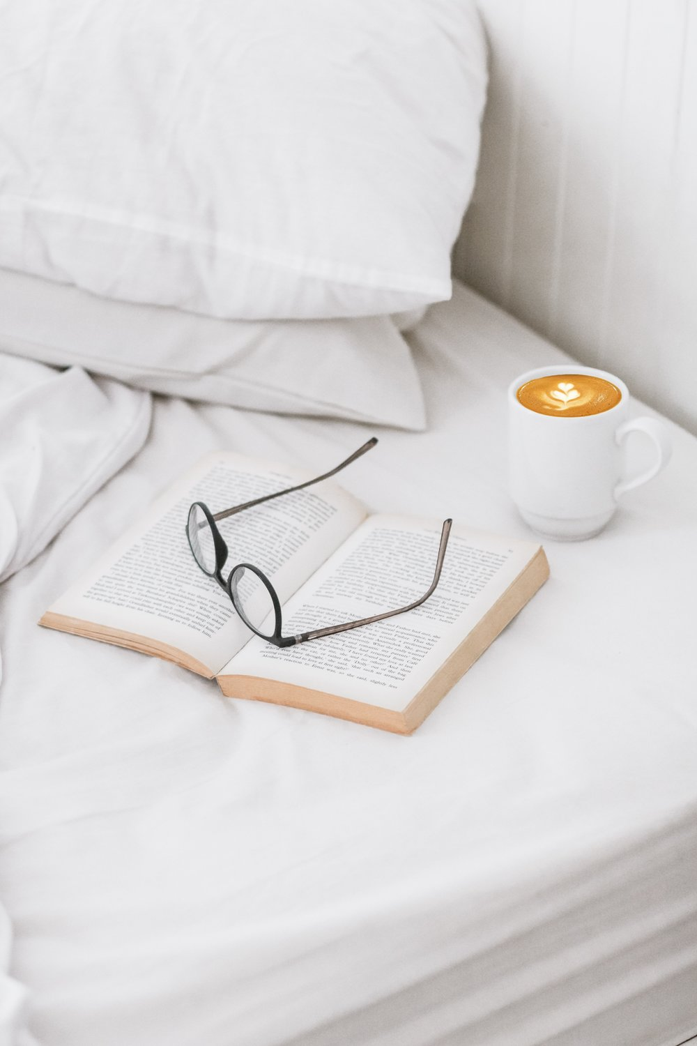 A bed with a coffee, book and pair on glasses
