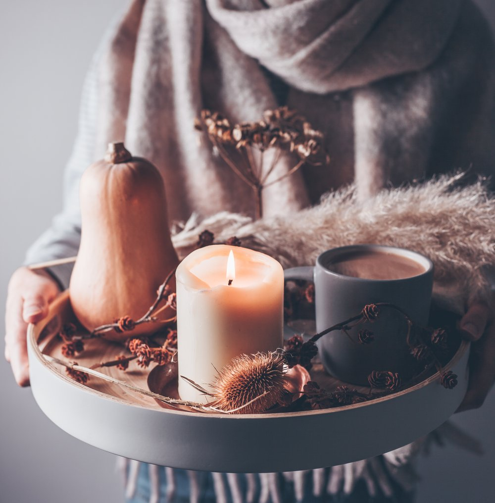 A woman carrying a candle and hot drink on a tray